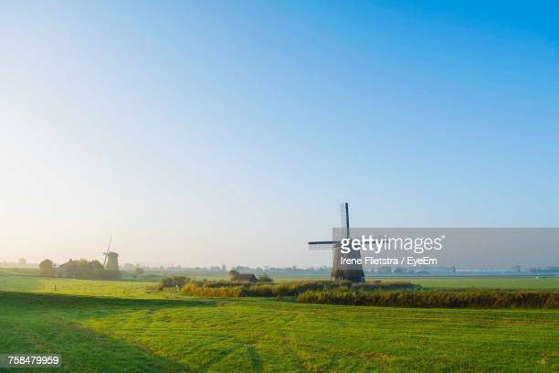 windmill on field against clear blue sky - traditional windmill stock photos and pictures