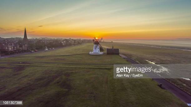 windmill on field against sky during sunset - lytham st. annes stock photos and pictures