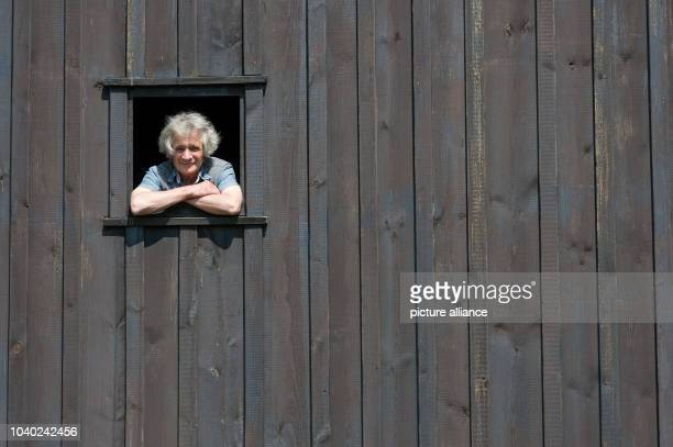 Windmill owner Detlef Sommerfeld looks out a small window in the post mill in Wilhelmsaue Germany 12 May 2016 The post mill was built between 1883...