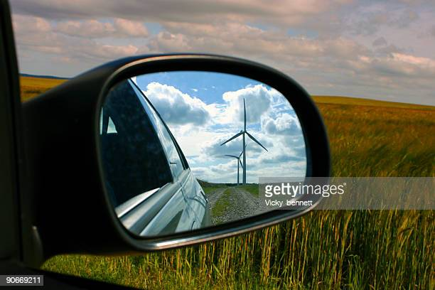Windmill reflected in car wing mirror with view of fields.