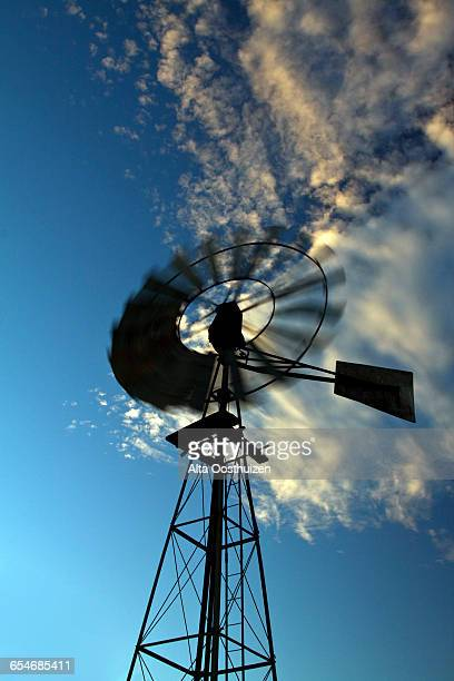 Windmill silhouette against a blue sky with white clouds moving - Graaff Reinet South Africa