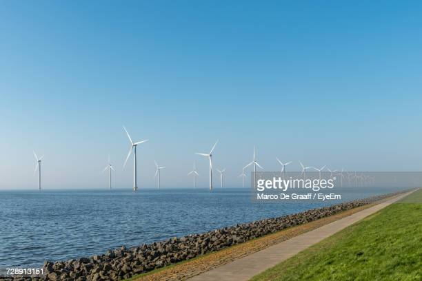 windmills against clear blue sky - traditional windmill stock photos and pictures