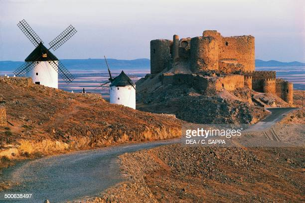 Windmills along the road of Don Quixote at Consuegra with La Muela Castle in the background CastillaLa Mancha Spain