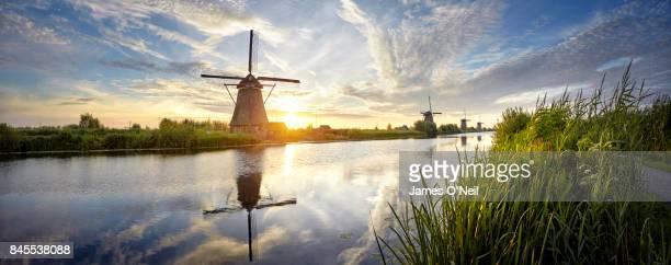 windmills and river at sunrise panoramic, kinderdijk, netherlands - niederlande stock-fotos und bilder