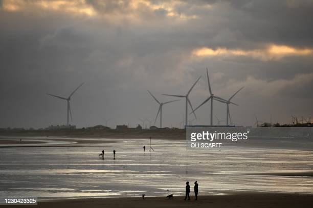 Windmills are seen as people exercise with their dogs on the beach in Bridlington, north east England, on January 4, 2021 - Britain's Prime Minister...