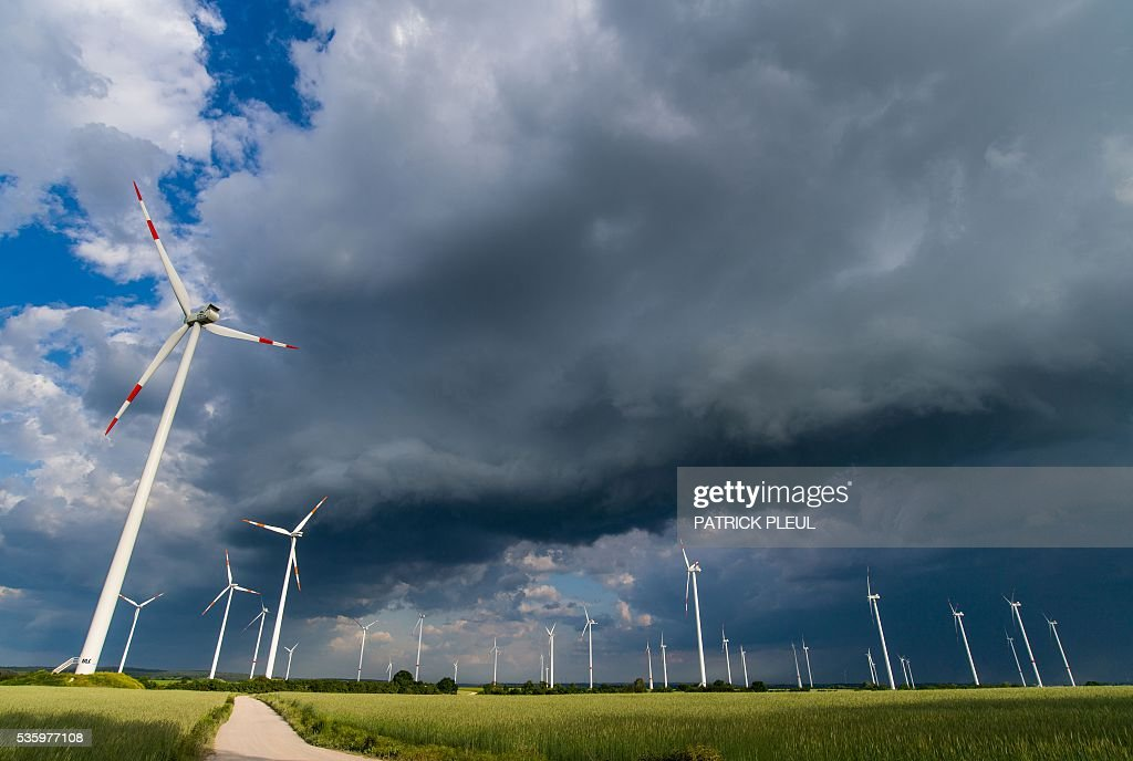 Windmills are seen on a meadow as a thunder cell crosses Sieversdorf, northeastern Germany, on May 30, 2016. / AFP / dpa / Patrick Pleul / Germany OUT