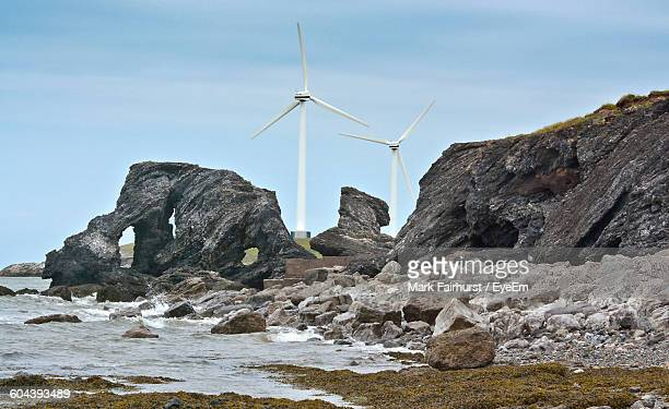 Windmills At Beach Against Sky