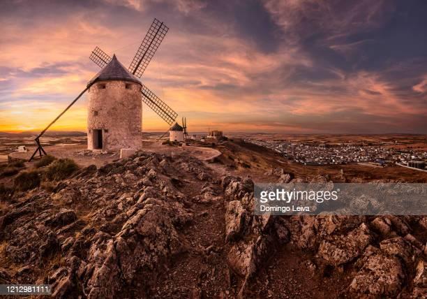 windmills at sunset in castilla la mancha, spain - castilla la mancha fotografías e imágenes de stock