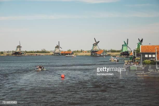 windmills by lake against sky - bortes photos et images de collection