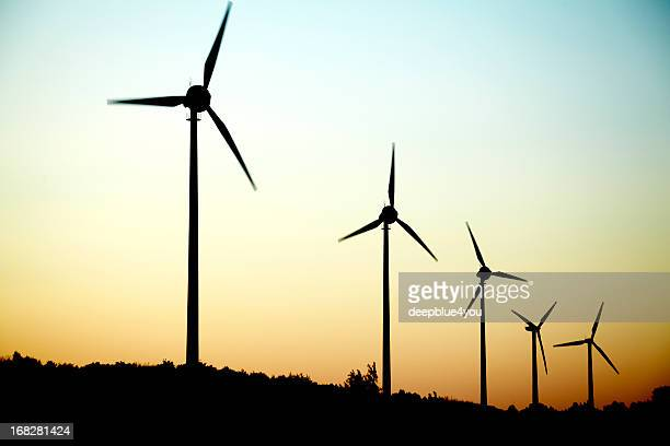 windmills in a row at dusk - paper windmill stock photos and pictures