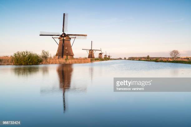 windmills in a row on the canal, kinderdijk, unesco world heritage site, molenwaard municipality, south holland province, netherlands, europe - キンデルダイク ストックフォトと画像