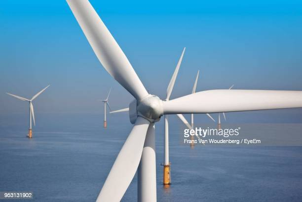 windmills in sea against sky - wind turbine stock pictures, royalty-free photos & images