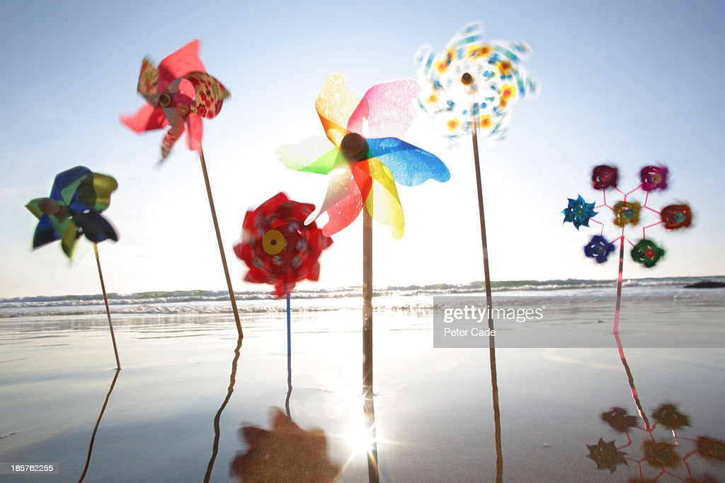 Windmills in the sand at the waters edge : Stock Photo