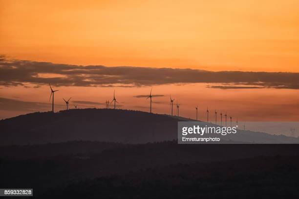 Windmills on a hill range at sunset in Cesme.
