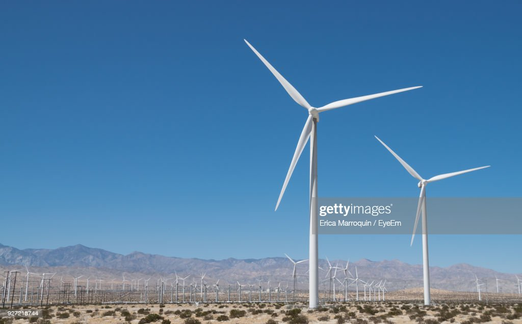 Windmills On Field Against Clear Blue Sky : Stock Photo