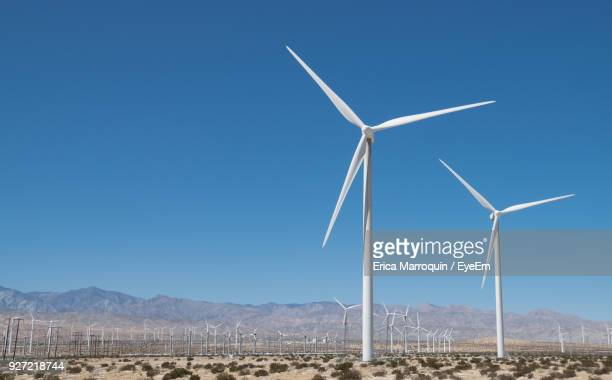 windmills on field against clear blue sky - wind turbine stock pictures, royalty-free photos & images