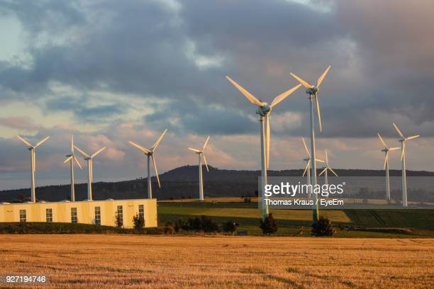 Windmills On Field Against Cloudy Sky During Sunset