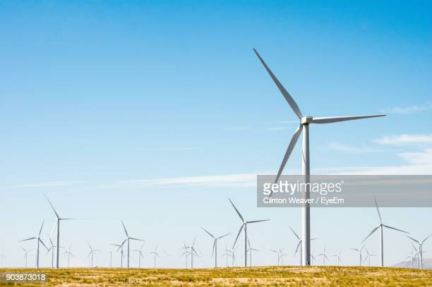 windmills on field against sky - traditional windmill stock photos and pictures