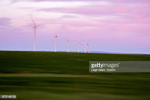 windmills on grassy field against cloudy sky at dusk - leigh grant stock pictures, royalty-free photos & images