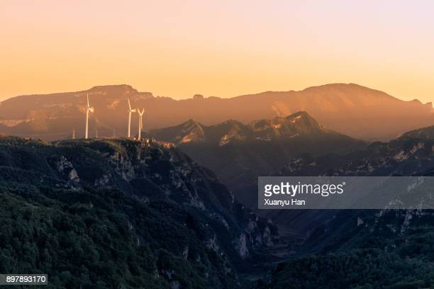 Windmills On Mountain Against Sky During Sunset