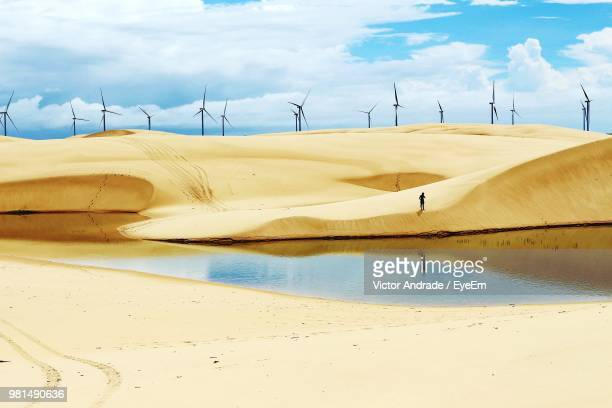 windmills on sand at beach against cloudy sky - latin america stock pictures, royalty-free photos & images