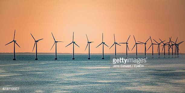 Windmills On Sea Against Orange Sky