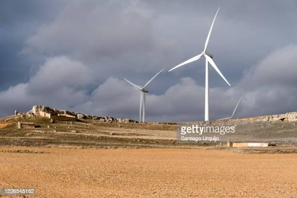 windmills under a stormy sky - 休耕田 ストックフォトと画像