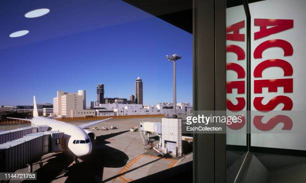 window airport with access billboard poster and plane connected to gate - transportation building type of building stock photos and pictures