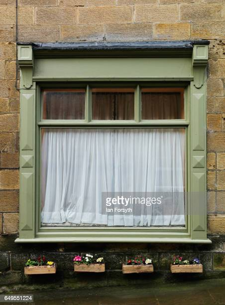 Window boxes filled with flowers are fastened to the wall of a hone in Robin Hood's Bay on the North Yorkshire coast on March 8 2017 in Robin Hood's...