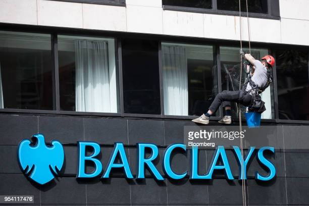 A window cleaner suspended from ropes cleans a window above a bank branch of Barclays Plc in London UK on Thursday May 3 2018 Barclays Plcis...