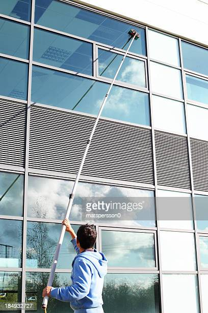 window cleaner using the water fed pole system - window cleaning stock photos and pictures