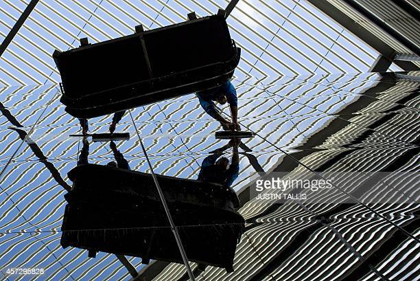 Window cleaners are reflected in a glass buliding in central London on October 16 2014 AFP PHOTO / JUSTIN TALLIS