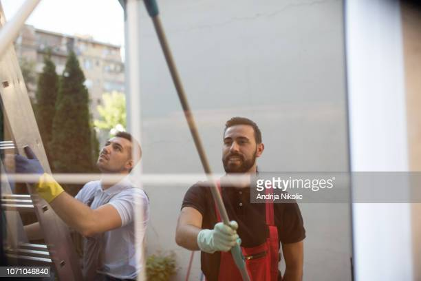 window cleaners working together - professional cleaning stock photos and pictures