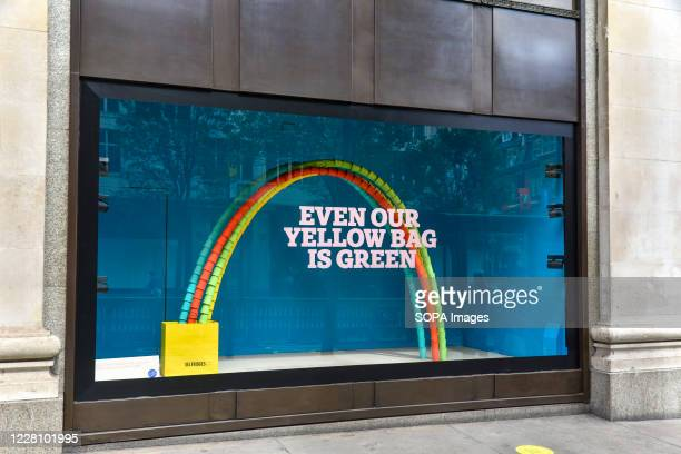 Window display in Selfridges with a sign saying 'Our iconic yellow bag contains 20% recycled coffee cups. The retailers new 'Project Earth'...