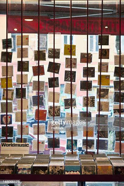 A window display of hanging compact discs in a record shop