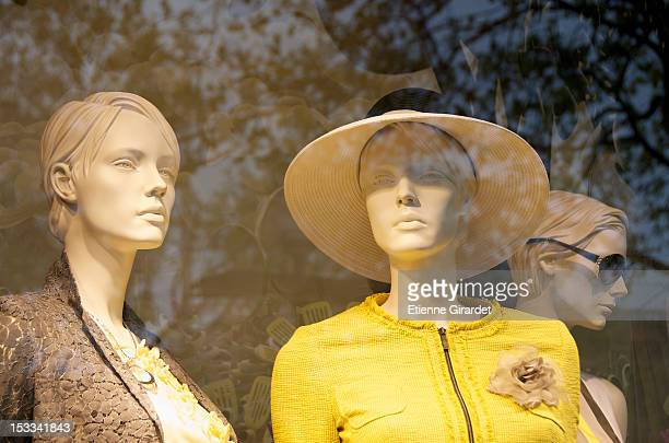 Window display of mannequins with reflection of trees