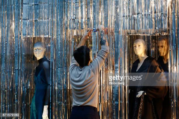 A window dresser creates a display in the window of Stradivarius fashion clothing store on Oxford Street in central London UK on Tuesday Nov 7 2017...