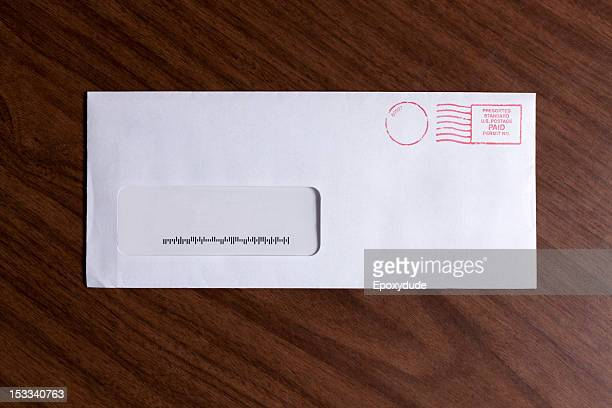 A window envelope with no address, but a barcode and red ink postage stamp