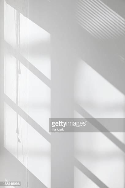 window glass, blinds and pulley shadows on wall - spiegelung stock-fotos und bilder