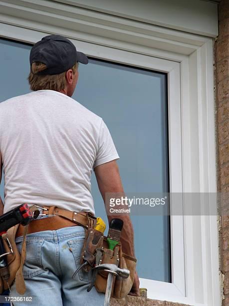 window installer with tool belt installing window