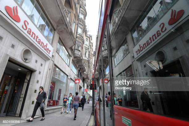 A window of a bus reflects signage of Banco Santander SA as it passes a bank branch in London UK on Tuesday Aug 15 2017 Banco Santander Spains...