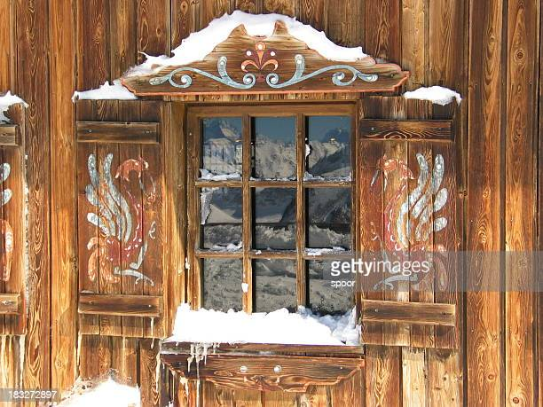 Window of a wooden snow hut with white landscape reflected
