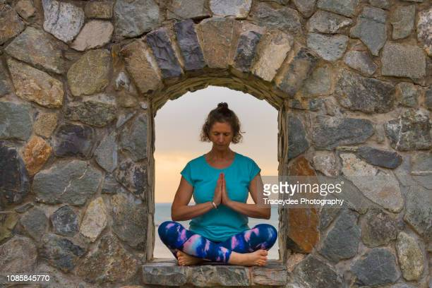 a window of opportunity for meditation in yoga for women aged 50 years and older - 55 59 years stock pictures, royalty-free photos & images