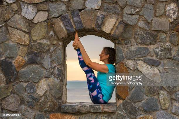 a window of opportunity for stretching in yoga for a woman aged 50 years and older - 55 59 years stock pictures, royalty-free photos & images