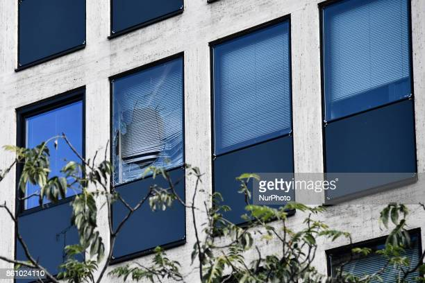 Window of the UIMM building breaks as a fireworks rocket is launched by the Metallurgy workers in Paris on October 13 2017 Several thousand workers...