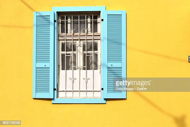 Window On Yellow Wall Of Building