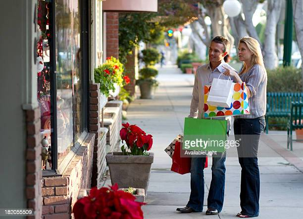 Window shopping young adult couple carrying bags
