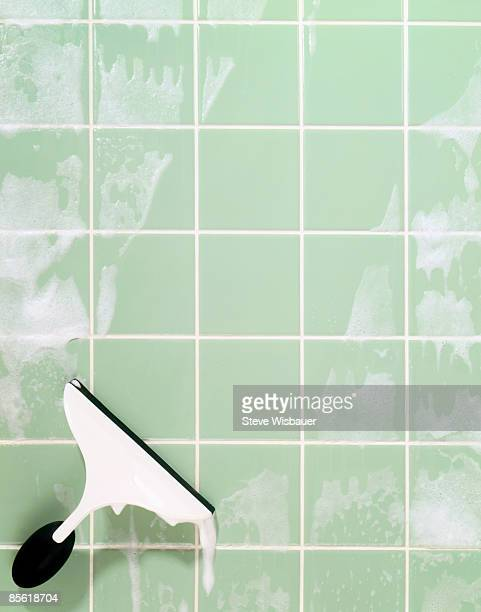 window squeegee cleaning soap suds on green tile