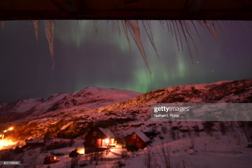 Window view from a cabin overlooking the northern lights above another cabin : Stock Photo