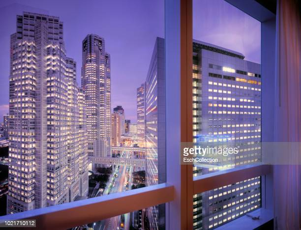Window view of illuminated Shinjuku business district, Tokyo, Japan